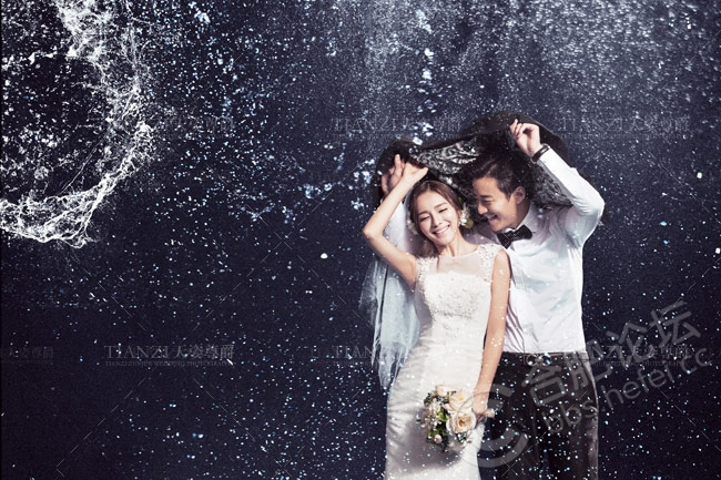 2、雨景婚纱摄影技巧要点讲解 雨天拍摄,常常会出现曝光过度的现象。因为雨天景物反差小,曝光过度会使反差更小,照片看起来是灰蒙蒙一片。所以,一般多采用减少曝光,延长显影的办法来改善。 3、透明的雨伞将光线折射的尤其完美 雨景婚纱照的拍摄一定要选择深色背景,拍雨景时,要选择深色背景,把明亮的雨丝衬托出来。如果画面中有水,不论是河湖水面,或是街道上的积水,雨点落在水面上溅起的一层层涟漪,也有助于雨景的表现。深色背景让雨丝完美显现,雨景婚纱摄影对快门速度要求很高