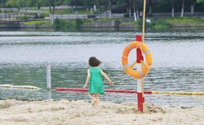 夕阳下的塘西河沙滩是孩子们避暑度假的乐园